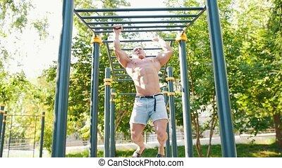 Muscular young man exercising on horizontal bar outdoors