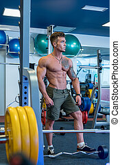 Muscular young man posing in fitness room