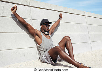 Muscular young man sitting on beach looking happy