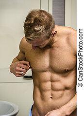 Muscular young man touching nipple piercing