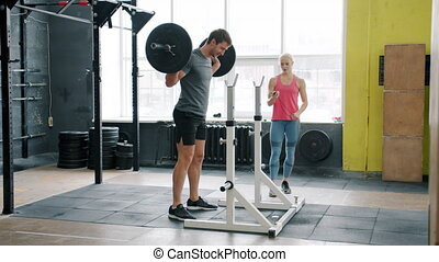 Muscular young man training in gym squatting with barbell working out with coach