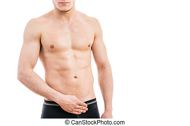 Muscular young man wearing boxer briefs isolated on white background.