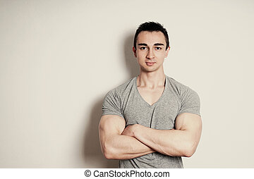 muscular young man with arms crossed standing against wall with copy space