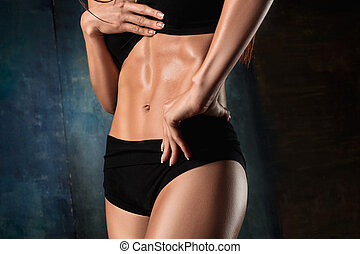 Muscular young woman athlete on black