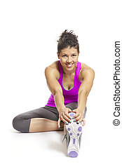 Young woman stretching leg in sports outfit smiling on white background