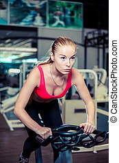 Muscular young woman working out on the exercise bike at the gym, intense cardio workout.