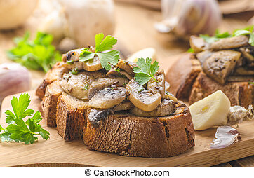 Mushroom mixture with olive oil on rustic bread with garlic, bio mushrooms and delicious herbs on top