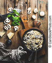 Italian style dinner. Creamy mushroom pasta spaghetti in cast iron pan on wooden boards with Parmesan cheese, fresh basil leaves and pepper over old rustic background. Top view, vertical composition
