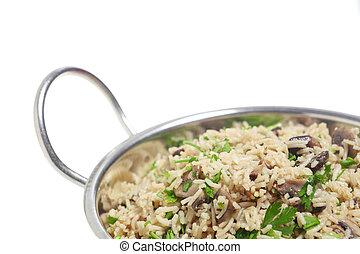 Close-up view of a mushroom pilau, made with basmati rice, in a kadai bowl.