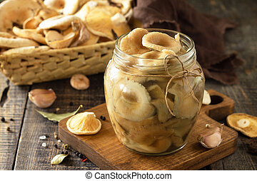 Mushroom preservation. Home preservation of products: glass jars with pickled mushrooms with spices on a rustic wooden table.