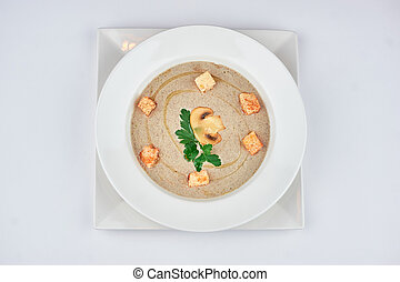 mushroom soup puree with breadcrumbs and herbs on a white background