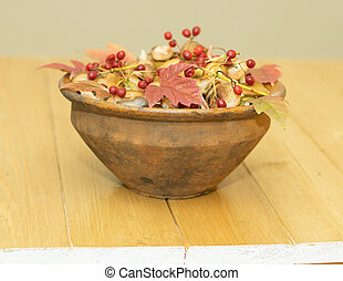 mushrooms and berries of viburnum in an old clay bowl on a wooden table.