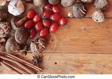Mushrooms and vegetables on wood background.
