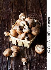 mushrooms in a basket on dark boards