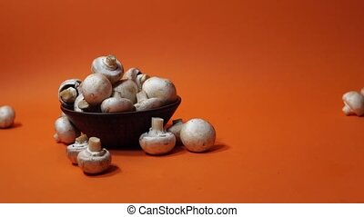 Mushrooms in a wooden bowl on an orange background. The ...