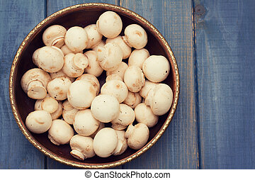 mushrooms in bowl on blue wooden background