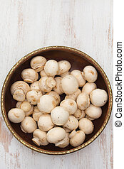 mushrooms in bowl on white wooden background