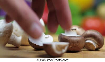 Mushrooms on chopping board with blurred vegetables