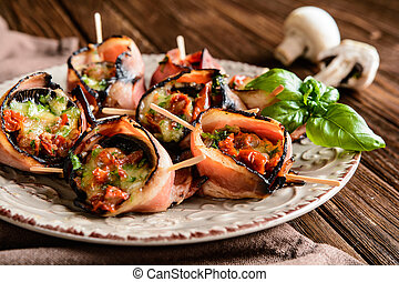 Mushrooms stuffed with cheese, sun dried tomatoes and wrapped in bacon
