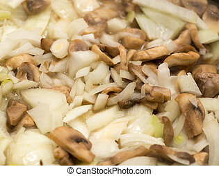 Mushrooms with onions are fried in a frying pan
