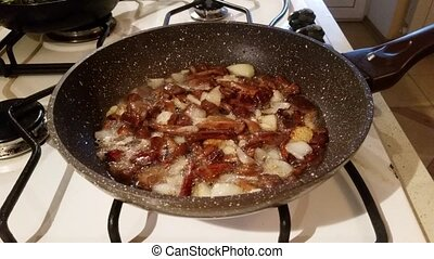 Mushrooms with onions are fried in a pan - Fresh honey...