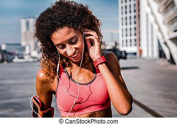 Pleasant good looking woman wearing her headphones