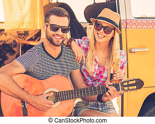 Music break during road trip. Handsome young man sitting in minivan and playing guitar while his cheerful girlfriend bonding to him and smiling