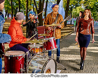 Music buskers with girl violinist on autumn outdoor.