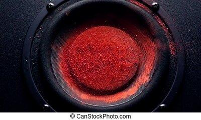 Music caption on orange powder over trembling loudspeaker....