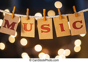 The word MUSIC printed on clothespin clipped cards in front of defocused glowing lights.