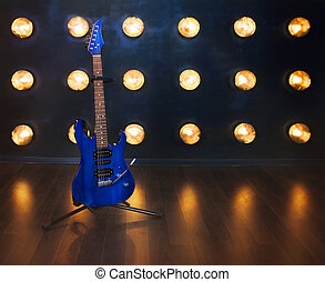 Music concept. Electric guitar standing on the wooden floor near