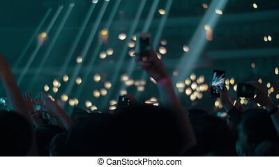 Music fans in concert hall waving lights and shooting with cellphones