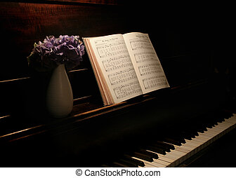 purple flowers in vase and hymnal open on old piano