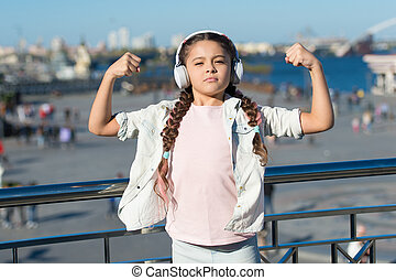 Music has healing power. Adorable child enjoy music playing in earphones on urban background. Little girl enjoying her favorite music outdoor. Cute small kid listening to energetic music in headset