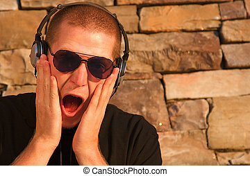 A cool young man listens to music on some headphones