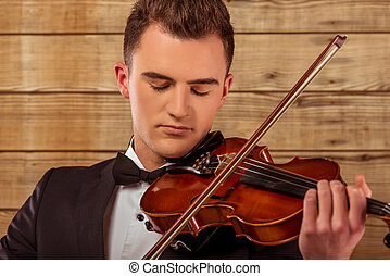 Music instrument violin - The young musician man playing...