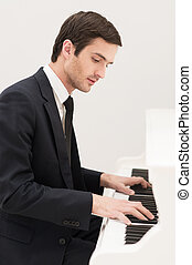 Music is everything. Confident young man in formalwear playing piano