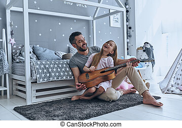 Music is so much fun. Young father teaching his little...