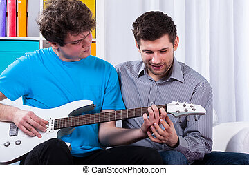 Boy learning to play on electric guitar on private lesson