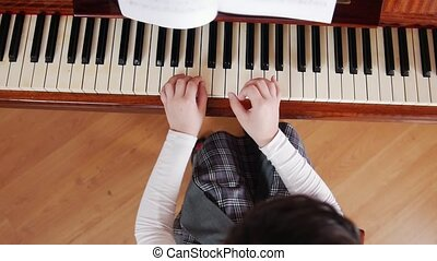 Music lesson. Girl learn to play the piano. View from the top