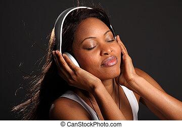 Headshot of beautiful happy black girl wearing headphones, listening to music with eyes closed.