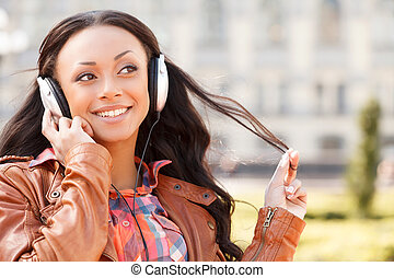 Music lover. Young African descent woman in headphones listening to the music and smiling
