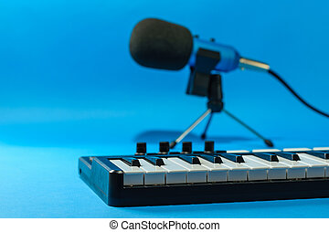 Music mixer and blue microphone with wires on blue background.