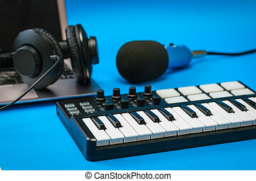 Music mixer, laptop and blue microphone with wires on blue background.