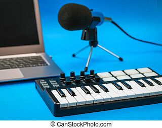 Music mixer, laptop and microphone with wires on blue background.