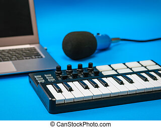 Music mixer, open laptop and microphone with wires on blue background.