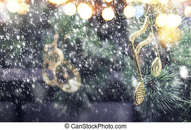 Music note decoration on christmas tree with snow falling in the winter