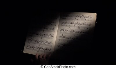 Music notes with ray of light, hand scrolls the sheet, on black