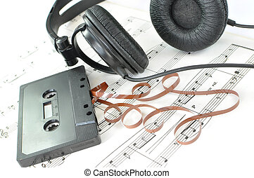 Old unwound cassette tape on a music sheet with headphones
