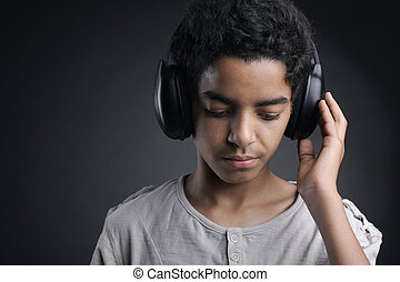 Portrait of african teenager listening music with headphones.